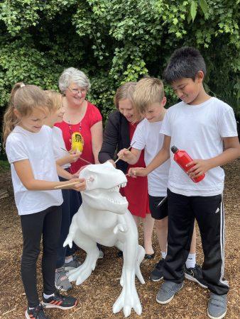 Diss school children painting t-rex sculpture